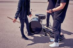 Partial view of rock band in black clothing standing near musical instruments. On street stock images