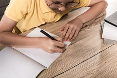 Partial view of schoolboy in eyeglasses writing in empty textbook at table with stack. Of books royalty free stock photo