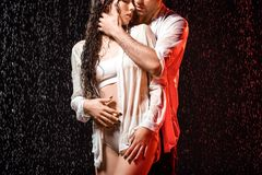 partial view of sexy couple in white shirts standing under rain