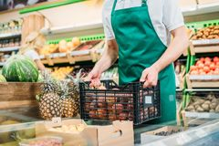 Partial view of shop assistant holding basket with fruits. In grocery shop Stock Photo