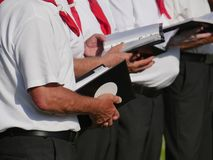 Partial view of 3 singers of a choir, holding in their hands textbooks, dark trousers, white short-sleeved shirt, red kerchief stock image