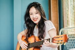 Partial view of smiling asian girl  playing on acoustic guitar while sitting on bed at home royalty free stock photo