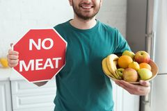 Partial view of smiling man. Holding no meat sign and bowl with fresh fruits vegan lifestyle concept royalty free stock image