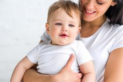 Partial view of smiling mother with cute little baby in hands. At home royalty free stock image