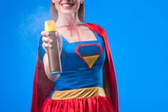 Partial view of smiling superwoman with detergent in hand. Isolated on blue stock image