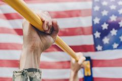 Partial view of soldier pulling himself up on crossbar with american flag. On backdrop royalty free stock photo