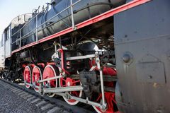 Partial view of a steam locomotive. Black metal boiler, red whee Royalty Free Stock Image