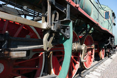 Partial view of a steam locomotive. Green metal boiler, red whee Stock Images