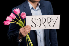 Partial view of stylish man holding tulips bouquet and sorry sign Stock Photo