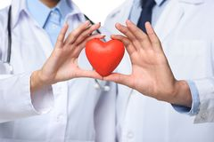 partial view of two doctors holding red heart in hands stock image