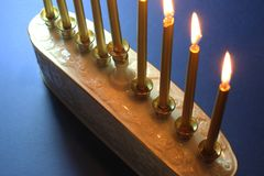 Partial view of a white ceramic menorah with gold candles against a blue background, backlit royalty free stock photography