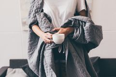 Woman in blanket with cup of coffee. Partial view of woman covered in blanket holding cup of coffee at home Royalty Free Stock Image
