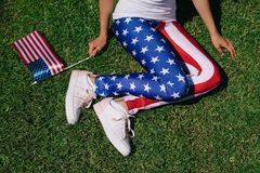 Partial view of woman with flagpole in leggins with american flag pattern resting on green lawn, americas independence day. Holiday concept stock image