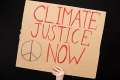 Partial view of woman holding placard with climate justice now lettering isolated on black, global warming concept