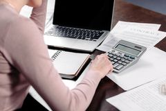partial view of woman making calculations at table with laptop and papers stock photo