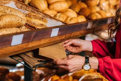 Partial view of woman taking paper bag for bread while shopping. In supermarket Royalty Free Stock Photography