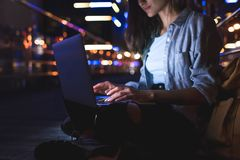 partial view of woman using laptop on street with night city lights stock image