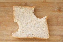 Partial whole grain bread slice. Whole grain bread slice  with bite taken Royalty Free Stock Image