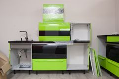 Partially assembled kitchen furniture with green cabinets with sink in countertop made of artificial stone. one cabinet is wrapped. In protective film stock photography