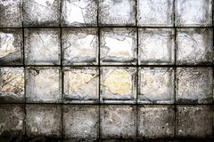 Partially broken, dirty window of glass blocks, on an abandoned farm, in the village. View from inside stock images