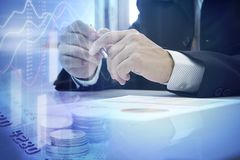 Making a decision on business investment. Partially close-up of business holding a pen while making a decision on business investment with lower copy space Stock Image
