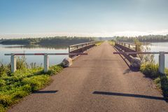 Partially closed road in and over a lake. Partially closed gate in front of a bridge and a road with water on both sides. It is a sunny day in the beginning of stock photography