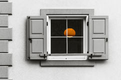 Orange Light. Partially coloured photo of an orange lamp visible through an open window during a rainy day Italy Stock Image