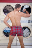 Partially Dressed In the Laundromat. Partially dressed man in Laundromat checks the time Stock Images