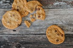 Partially eaten choc chip cookies seen fresh from the oven, on a rustic kitchen table. These large, home baked cookies are seen on a rustic wooden table, having Stock Images