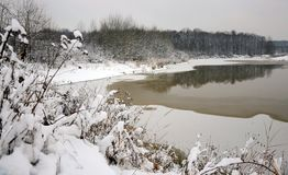 Partially frozen lake near forest Stock Photos