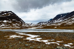 Partially frozen lake in snowy arctic mountains. Partially frozen lake by a walking trail in snowy arctic mountains. Sky is cloudy Royalty Free Stock Photography