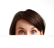 Partially hidden face with big blue eyes. Face with big blue eyes partially hidden behind a white empty board Royalty Free Stock Image