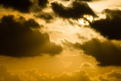 Partially hidden sun among dark clouds Stock Photography