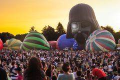A row of hot air balloons at a balloon festival, with a large crowd. Partially inflated hot air balloons, one of them shaped like Darth Vader`s helmet, rise royalty free stock photos