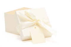 Partially opened cream colored gift box. With attached bow and name tag; white background stock photography