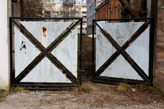 Partially rusted open heavy metal doors with black frame and sheet metal fillings preventing access to abandoned backyard. Partially rusted open heavy metal royalty free stock image
