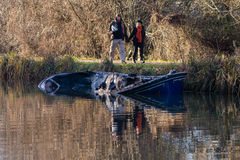 Partially submerged canal boat after fire with onlookers. Bath, UK - January 2 2017:  Damaged hull of narrow boat in Kennet and Avon Canal after being gutted by Royalty Free Stock Photography