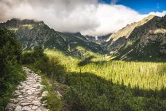 Partially Sunlit Valley with Hiking Trail and Peaks of Mountains stock image