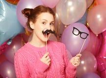 Partibegrepp: den lyckliga flickan med fejkar mustascher och exponeringsglas royaltyfri bild