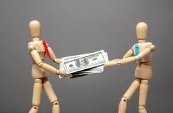 Participación en los beneficios entre los socios Dos hombres de negocios dividen dólares del efectivo entre ellos mismos Lucha pa fotografía de archivo