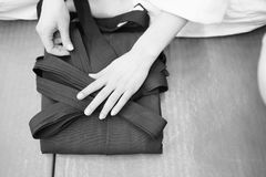 Participant adds the underside of the hakama aikido clothing. The training participant adds the undere of the hakama aikido clothing Stock Photos