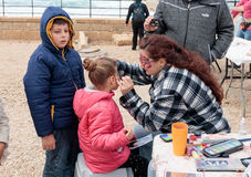 Participant of festival drawing butterfly on the girl`s face. Caesarea, Israel, March 11, 2017 : Participant of the Purim festival applies a butterfly drawing on royalty free stock photos