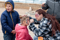 Participant of festival drawing butterfly on the girl`s face. Caesarea, Israel, March 11, 2017 : Participant of the Purim festival applies a butterfly drawing on stock photography