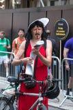 Participant habillé en tant que vélo se tenant prêt femelle regardant une carte chez Pride Parade gai, Londres 2018 images stock