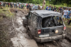Participant on Jeep passes a deep muddy pit. Stock Photos