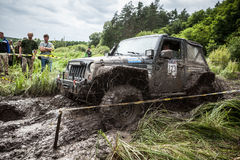 Participant on Jeep passes a deep muddy pit. Royalty Free Stock Photography