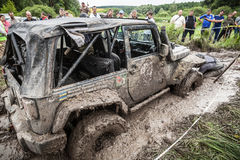 Participant on Jeep passes a deep muddy pit. Royalty Free Stock Photos