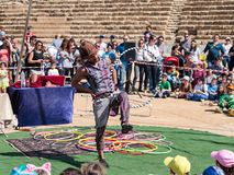 A participant of the Purim festival juggles with hoops for visitors in Caesarea, Israel. Caesarea, Israel, March 03, 2018 : A participant of the Purim festival Stock Image