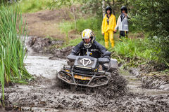 The participant on quad bike passes a deep water pit. Royalty Free Stock Photo