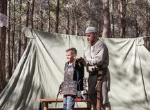 The participant of the reconstruction `Viking Village` Helps the visitor to wear armor in the camp in the forest near Ben Shemen i. Ben Shemen, Israel, November Royalty Free Stock Photography